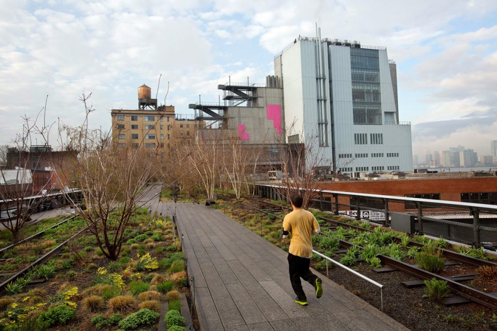 In this Tuesday, April 21, 2015 photo, a runner on New York's High Line runs toward the Whitney Museum of American Art, right. The Whitney opens the doors to its new home on May 1. It's an asymmetrical structure with sweeping views of the High Line and the Hudson River. (AP Photo/Mark Lennihan)