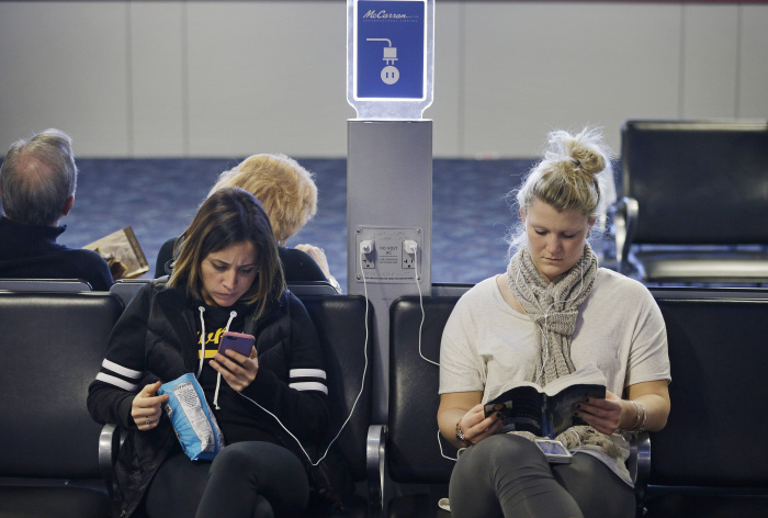 FILE - In this Dec. 29, 2014, photo, travelers use a charging station at McCarran International Airport in Las Vegas. While the common lithium-ion battery that's used to power laptops, cellphones and tablet computers has improved in recent years, the demand that us gadget addicts are placing on these batteries has soared. (AP Photo/John Locher, File)