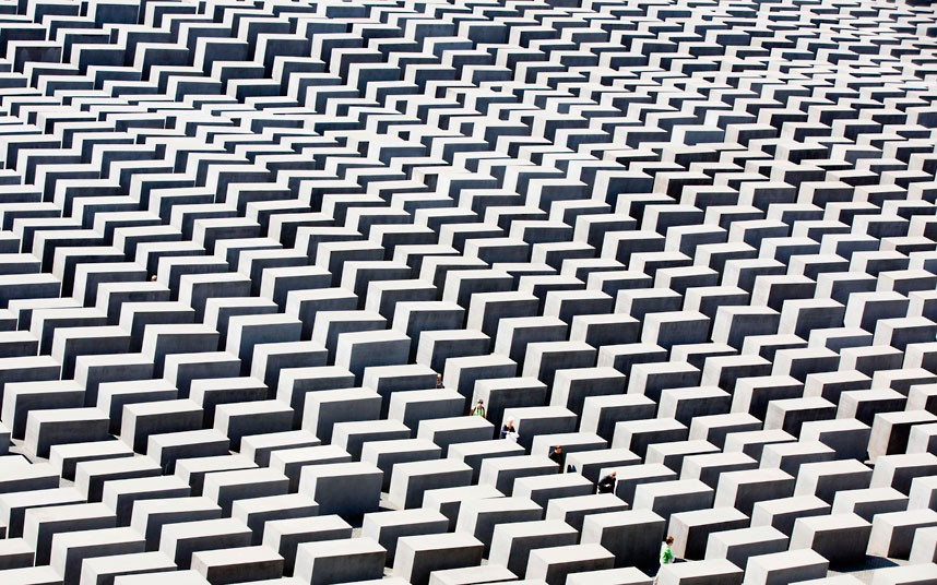People walk through the concrete blocks of the the Holocaust memorial in Berlin, Germany, Monday, Aug. 13, 2012. The memorial to the 6 million Jews killed in Europe under the Nazis was created by U.S. architect Peter Eisenman and consists of an undulating field of 2,711 blocks through which visitors can wander. (AP Photo/Gero Breloer)
